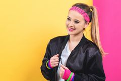 Woman in 1980`s fashion theme. On a split yellow and pink background royalty free stock images