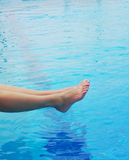 Woman`s feet against blue water of the pool. Royalty Free Stock Photos