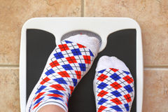 Woman's feet on bathroom scale stock image
