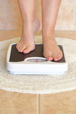 Woman's feet on bathroom scale Royalty Free Stock Images
