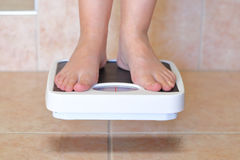 Woman's feet and bathroom scale Royalty Free Stock Photos