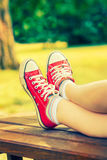 Woman`s feet in bright red canvas sneakers stock image