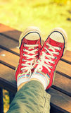 Woman`s feet in bright red canvas sneakers Stock Images