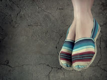 Woman`s feet with canvas worn shoes resting against a cemented floor. Horizontal shot of off-centered female feet with worn canvas shoes, with dark vignette and Royalty Free Stock Photos