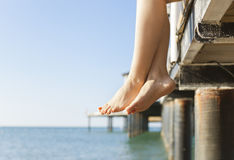 Woman's feet dangle from jetty royalty free stock photos