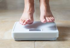 Woman Floating Slightly Above Surface of Weight Scale Royalty Free Stock Image