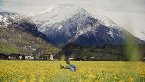Woman`s feet in jeans in the air and pedaling of imaginary bicycle. Woman is lying and training in the field with. Dandelion flowers in mountain valley 4k stock footage