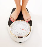 Woman's feet on large weighing scales Royalty Free Stock Photography