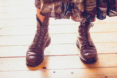 Woman's feet in leather boots on wooden floor Stock Photos