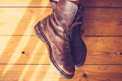 Woman's feet in leather boots on wooden floor Royalty Free Stock Photo