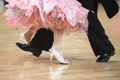Woman`s feet between man`s feet dancing on parquet floor stock image