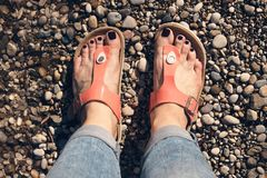 Woman`s feet in orange sandals and jeans standing royalty free stock photography
