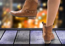 Woman`s feet with Party boots over night city. Digital composite of Woman`s feet with Party boots over night city Stock Photo