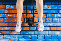 Woman`s feet and photo camera dangling in front brick wall. Woman`s feet and photo camera dangling in front of blue and orange brick wall stock photos