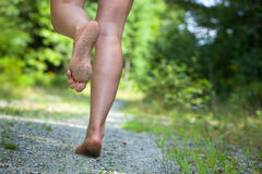 Woman's feet running on gravel road Royalty Free Stock Photography