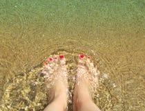 Woman`s feet on the sand beach with crystal transparent waves. Sy. Mbol of vacation. Koukounaries Beach. Skiathos island, Sporades archipelago. Greece stock photo