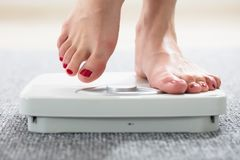 Woman`s Feet On Scale. Close-up Of A Woman`s Feet On Weighing Scale Over The Carpet royalty free stock image
