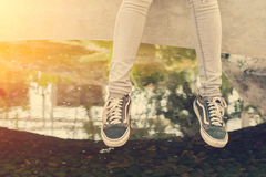 Woman`s feet in a sneakers Sitting  near the lake. Legs of woman`s feet in a sneakers Sitting  near the lake Stock Photography