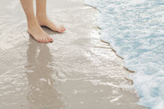 Woman`s feet standing in surf at the beach Royalty Free Stock Photo