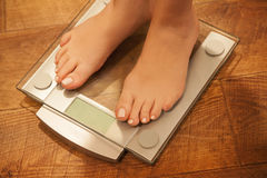 Woman's feet standing on weight scale. Royalty Free Stock Photography