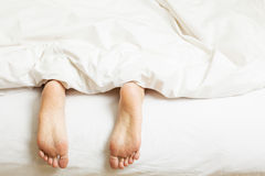 Womans Feet Sticking Out Of Blanket On Bed Royalty Free Stock Images