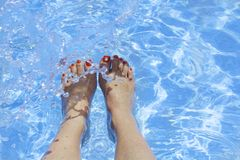 Woman`s feet in a swimming pool under water. Beautiful feet with Royalty Free Stock Photos