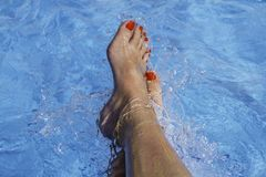 Woman`s feet in a swimming pool under water. Beautiful feet with Royalty Free Stock Photo