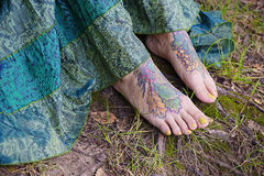 Woman's feet with a tattoo Stock Photography