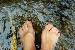 Woman's feet underwater. Woman's feet under fresh water stock photo