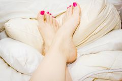 Woman`s feet, up on the pile of soft pillows stock photos