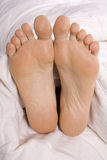 Woman's feet in white covers Royalty Free Stock Photos