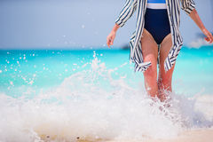 Woman's feet on the white sand beach in shallow water Royalty Free Stock Image