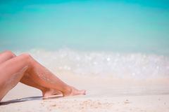 Woman's feet on the white sand beach in shallow water Stock Images