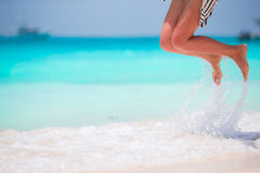 Woman's feet on the white sand beach in shallow water Stock Image