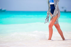 Woman's feet on the white sand beach in shallow water Stock Photos