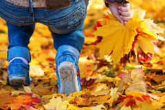 Woman's feet on a yellow autumn leafs background Stock Photography