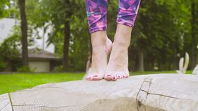 Woman`s feets doing exercises on wooden log. Close up of woman`s feets doing exercises on wooden log stock video footage