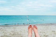 Woman's feets on the sea shore Stock Photography
