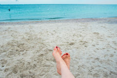 Woman's feets on the sea shore Royalty Free Stock Image