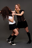Woman's fight. Women in short skirts is fighting against dark background Stock Images