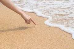 Woman`s finger is drawing on beach sand Royalty Free Stock Photography