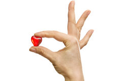 Woman's finger Holding a Heart Shaped on white Background Stock Photography