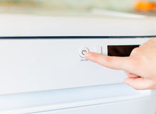 Woman's finger is pushing on button on/off. On dishwasher royalty free stock photo