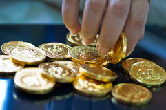 Woman's fingers holding gold coins Stock Image