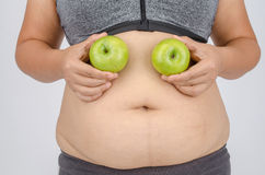 Woman's fingers measuring her belly fat Stock Photos