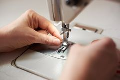 Beginning of sewing process. Woman`s hands pulling loop threads through the presser foot. Close up view. Woman`s fingers putting thread in needle loop on royalty free stock photography