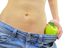 Woman's fit belly with green apple and oversized jeans Stock Images