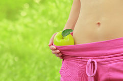 Woman's fit belly with green apple and oversized pants Stock Photo