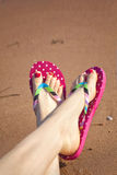 Woman's Flip Flps. Painted toes and flip flops on a sandy beach royalty free stock photo