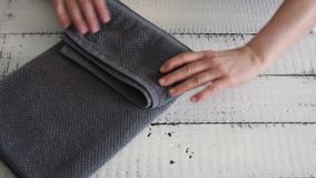 Woman`s folding a grey towel to place it on the shelf. stock footage